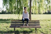 Portrait de jeune femme assise sur le dossier du banc de parc — Photo de stock