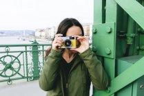 Венгрия, Будапешт, Молодая женщина на мосту Свободы фотографирует — стоковое фото