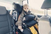 Маленький хлопчик, які сидять на задньому сидінні автомобіля seat — стокове фото
