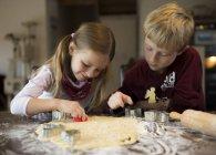 Menino e menina cortando biscoitos com cortador de biscoitos — Fotografia de Stock