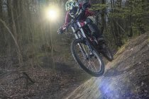Male biker free-riding in forest at daytime — Stock Photo