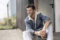 Laughing man wearing denim jacket sitting on stair — Stock Photo