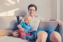 Padre e hijo sentados en el sofá con portátil - foto de stock