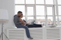 Пара сидящих на подоконнике с помощью ноутбука — стоковое фото