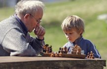 Grandfather and grandson playing chess outdoors — Stock Photo