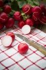 Rabanetes cortados ao meio e vermelhas com a faca na toalha de cozinha — Fotografia de Stock