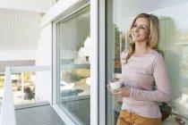 Frau steht mit Tasse Kaffee an Glasfront vor Haus gelehnt — Stockfoto