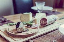 Placa de madeira com trufas, queijo e salame sobre mesa — Fotografia de Stock