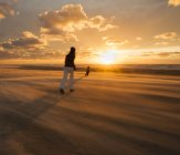 Denmark, Jutland, Lokken, mother catching child on stormy beach at sunset — Stock Photo