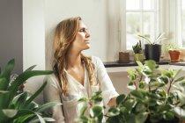Giovane donna seduta e ponderare tra le piante a casa — Foto stock