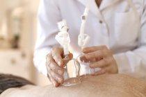 Femme senior traitant de femmes pratiquant alternatif avec ventouses vacuum thérapie — Photo de stock