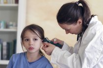 Girl sitting while pediatrician using otoscope for examination — Stock Photo