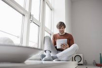 Man using digital tablet and sitting on window sill — Stock Photo