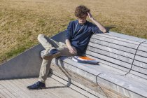 Germany, Baden-Wurttemberg, Teenage boy sitting on bench, learning — Stock Photo