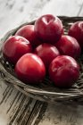 Bowl of red plums on shabby wooden table — Stock Photo