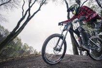 Motociclista maschio parassitismo nella foresta durante il giorno — Foto stock