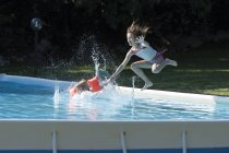 Enfants de sauter dans la piscine en plein air l'été — Photo de stock
