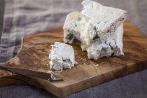 Close-up di pezzi di gorgonzola con il coltello da formaggio sul tagliere di legno — Foto stock