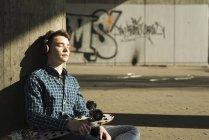 Подросток с скейтборд слушания музыки — стоковое фото