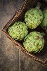 Panier d'artichauts biologiques sur une surface en bois sombre — Photo de stock