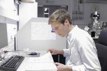 Cientista sentado em documentos de leitura de mesa — Fotografia de Stock