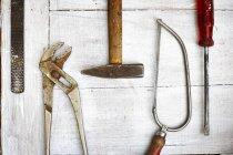 Файл, захвати, молоток, saw і гвинт драйвер на сірий дерева, підвищені подання — стокове фото