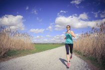 Donna che pratica jogging attraverso il paesaggio rurale — Foto stock
