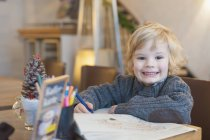 Garçon blond souriant dans un café, portrait — Photo de stock