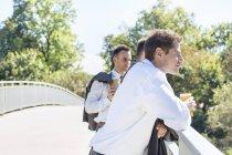 Collègues debout avec des gobelets jetables sur le pont dans la ville — Photo de stock