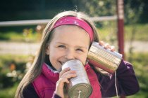Portait of little girl with tin can phone — Stock Photo