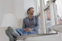 Расслабленный человек сидит на подоконнике — стоковое фото
