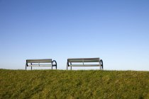 Две скамейки на холме с голубым небом на заднем плане — стоковое фото