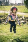Niña saltando la cuerda en el jardín - foto de stock