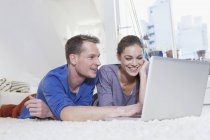 Couple lying on carpet at home and using laptop — Stock Photo