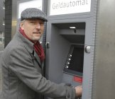 Человек, стоящий у банкомата — стоковое фото