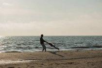 Дания, Ютландия, Lokken, отец, играя с дочерью на пляже — стоковое фото
