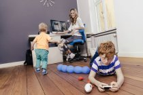 Mother with two sons playing in workroom — Stock Photo