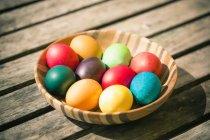 Gros plan du bol de Pâques coloré des œufs sur la table en bois — Photo de stock