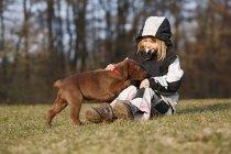 Девушка, сидящая на лугу и играющая с щенком-лабрадором — стоковое фото