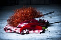 Metal shovel of chili threads and red chili peppers with kitchen towel on grey wood — Stock Photo