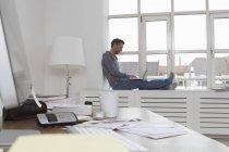 Mann sitzt auf der Fensterbank mit laptop — Stockfoto