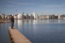 Alemania, Renania del Norte-Westfalia, Dortmund-Hoerde, lago Phoenix, Senior en paseo marítimo de madera en pie y mirando a ver - foto de stock