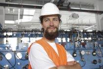 Рабочий в каске, стоящий в заводском зале со скрещенными руками — стоковое фото