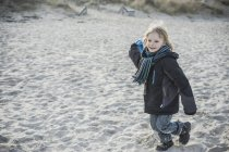 Smiling little boy running on beach in winter — Stock Photo
