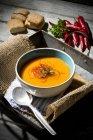 Karottensuppe mit Chili-Fäden in Schüssel auf Tablett mit Sackleinen — Stockfoto