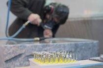 Schleifmaschine und Bildhauer arbeiten an Grabstein — Stockfoto