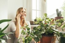 Smiling woman at home around potted plants — Stock Photo