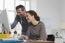 Man and woman at home sitting at desk with computer — Stock Photo