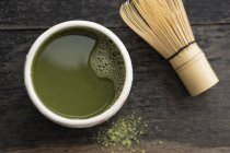 Elevated view of green Matcha tea in cup with Cha-sen on wooden table — Stock Photo