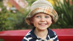 Ritratto di un ragazzino sorridente indossando cappello da sole — Foto stock